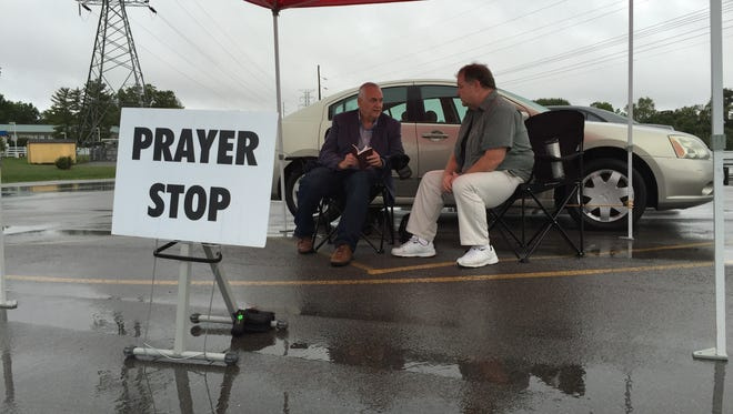 Scott Coy talks with David Haley about prayer in front of Victory Christian Center on Middle Tennessee Boulevard in Murfreesboro.