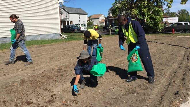 Workers from the non-profit Greening of Detroit scatter 85,000 worms on a vacant lot on East Forest in Detroit in September 2015.