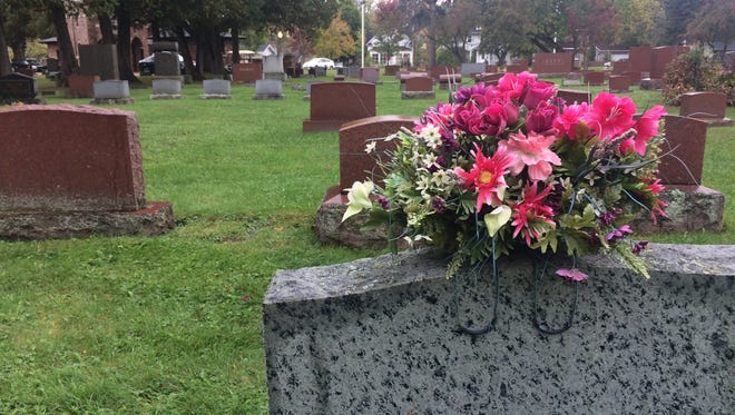 Flowers rest atop a gravestone at Pine Grove Cemetery in Wausau on Oct. 5, 2015.