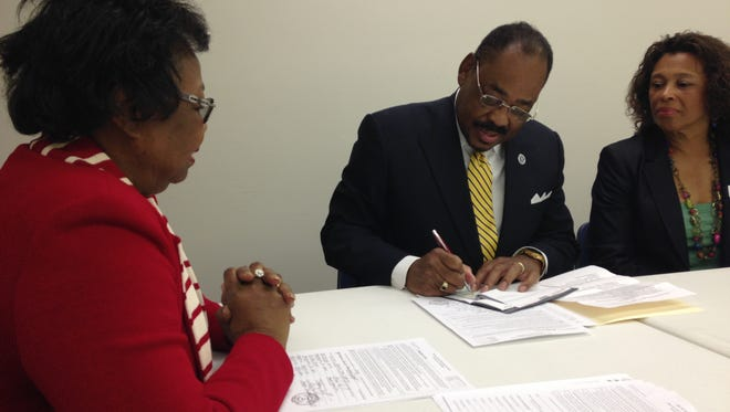 Dan Harris signs his qualifying check for Montgomery County Democratic Chair Dr. Tyna Davis (left) while Harris' wife Deborah (right) looks on.