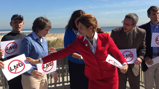 Sen. Jennifer Beck (R-Monmouth) hands out a sign opposing a proposed deepwater gas port off the coast of New Jersey at a press conference in Sea Bright on Oct. 6, 2015.