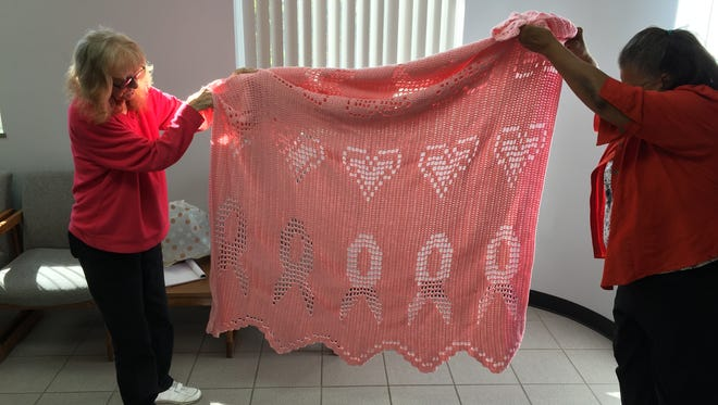 Gloria Adkins and the News Journal's Cathy Winburn hold up an afghan made for Adkins by her friend, Mary Jane Skinner. Adkins is a breast cancer survivor.
