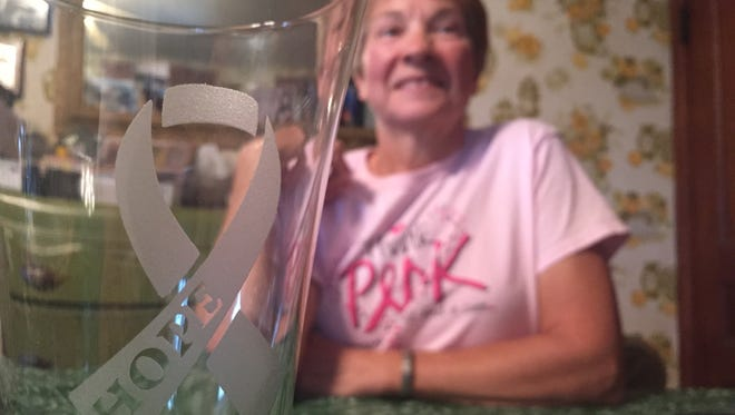 Martha Holbein raises money for cancer research by selling personalized glassware she sandblasts with cancer support messages .