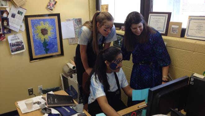 Program Director Julie Rigsby (standing), watches as student Mira Bhakta (seated) and student Lia Mosher (leaning), go over Thursday receipts. Face paint is from a pep rally.