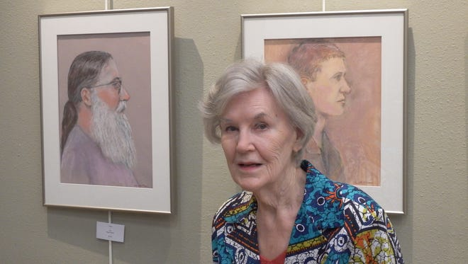 Ruth Muir, 90, of Coralville stands in front of her pastel portraits that are on display in the Johnson County Senior Center on Oct. 7, 2015. Her portraits are on display until Thanksgiving Day,