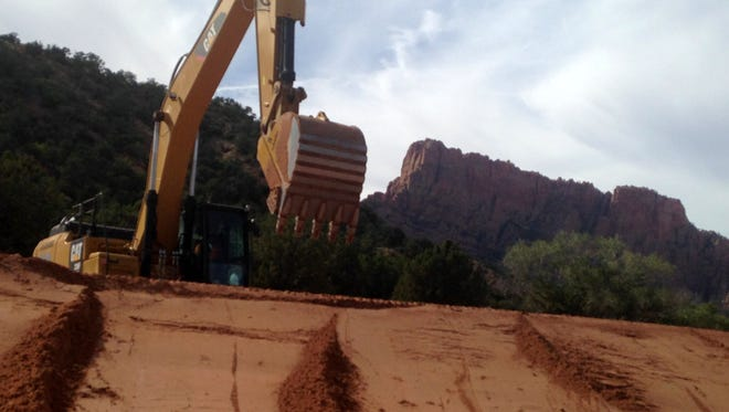 Contractors are using heavy equipment to repair roads and improve flood protection in Hildale, where state and federal emergency dollars are going toward improvements in the wake of a devastating flood that killed three mothers and 10 of their children on Sept. 14. This photo shows work going in alongside Canyon Street on Sept. 29, 2015.