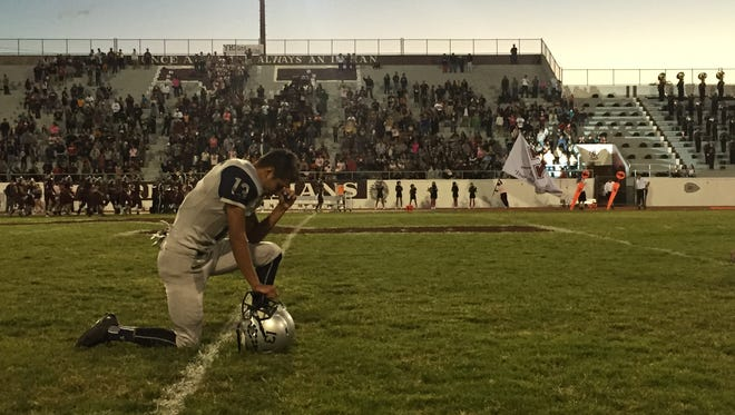 Oct. 8 2015: Del Valle's Jose Valenzuela prays before the game against Ysleta. Del Valle defeated Ysleta, 33-17.