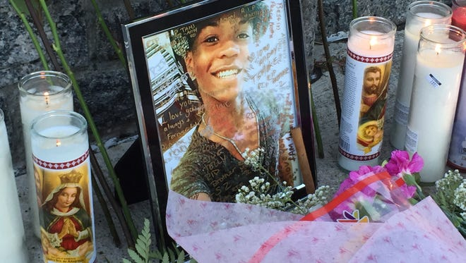 A memorial of flowers, candles is set up on Saturday in Sleepy Hollow's Barnhardt Park where Tahj Robinson, 17, was fatally stabbed the previous night. A picture frame of Robinson was also there, which friends penned messages on throughout the evening.