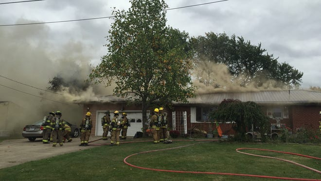 Firefighters work to extinguish a house fire on Taylor Road in Washington Township on  Tuesday.