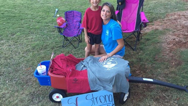 Simpsonville's Janet Kulig, right, and her 7-year-old daughter Kinsie have been selling t-shirts to raise money for Columbia flood victims.