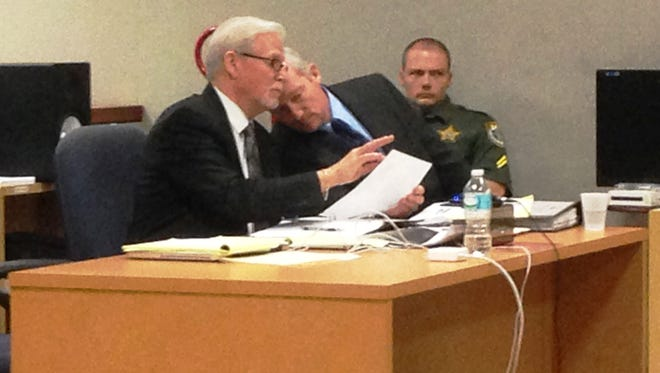 Defendant William Woodward leans in to listen to his attorney, Greg Eisenmenger, during a motion earlier this year.
