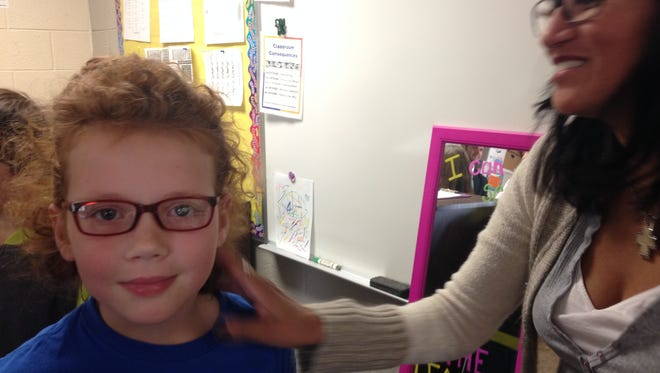 Melissa Howard, a fourth-grader at Algonquin Elementary School, is pleased with her new pair of prescription eyeglasses. Pearl Beach Lions Club led the project providing 64 glasses and 540 eye exams to students at the school.