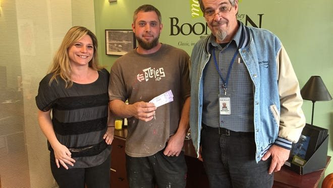 "Boonton Main Street Executive Director chris Manzella, left, and Daily Record reporter William Westhoven, right, present Daily Record zombie contest winner Jeremy Westfall with two tickets to see ""Evil Dead: The musical"" at the Mayo Performing Arts Center."