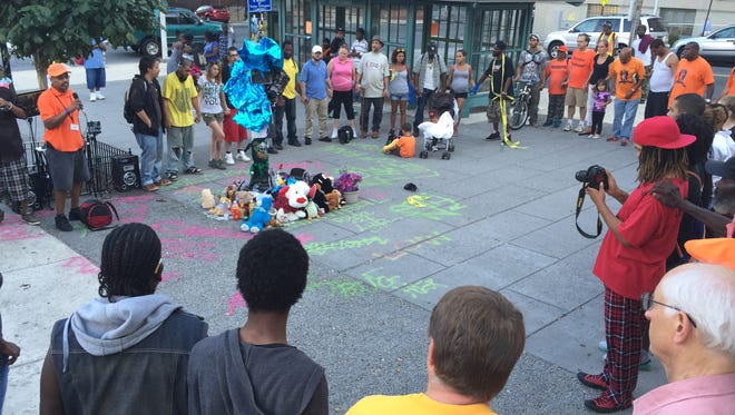 """More than 100 people, including members of the Wilmington PeaceKeepers group, form a circle around a memorial for Thomas L. """"Cannibal"""" Cottingham to pray for his family, as well as peace on the streets."""