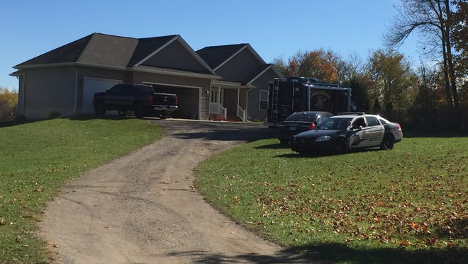 An Eaton County Sheriff's Office patrol car and a Lansing Police Department forensics van outside a home in Eaton Rapids Township where authorities said one person was shot and killed and another injured Tuesday night.