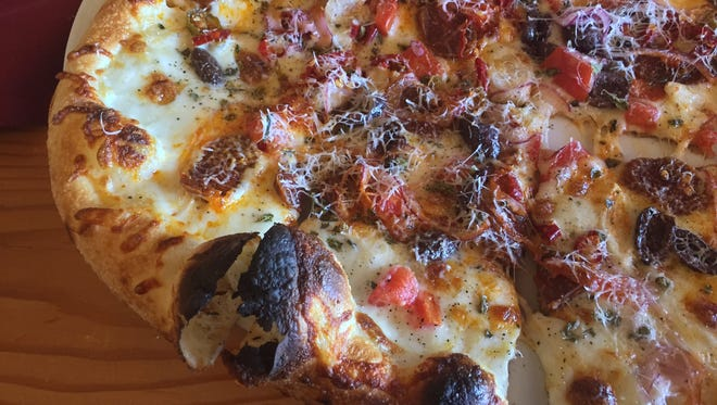 The Calabrian salame pizza at La Vecchia arrives thin, blistered and spicy from red chilis.