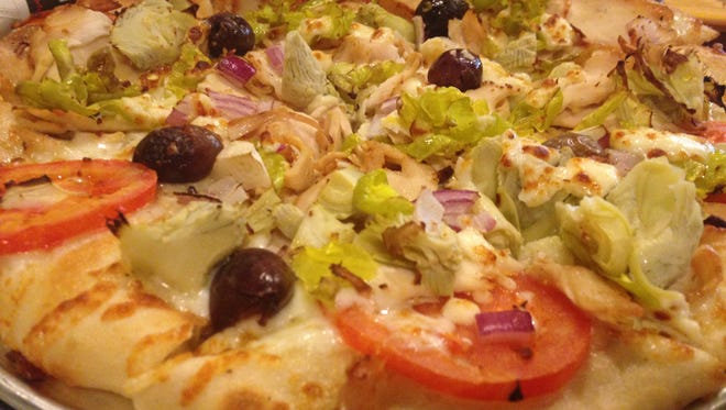 The Mediterranean artisan pizza includes sliced, flame-grilled chicken breast, ripe Roma tomatoes, imported kalmata olives, artichoke hearts, crunchy pepperoncinis, diced red onion, crumbled feta cheese and house-shredded mozzarella.
