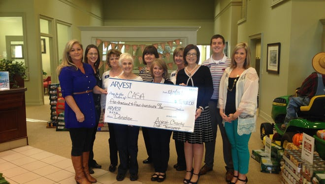 Court Appointed Special Advocates receives $5,400 from the Arvest Bank Charity Golf Tournament. Shown are, from left, Kristy Williams of CASA; Cindy Sutterfield and Mary Bailey, both of Arvest Bank; Betsy Short of CASA; Gail Mainord of Arvest Bank; Robyn Bradford of CASA; Cheri Adams of Arvest Bank; Gail Inman Campbell of CASA, and  Spencer Adams and Tiffany Watkins, both of Arvest Bank.