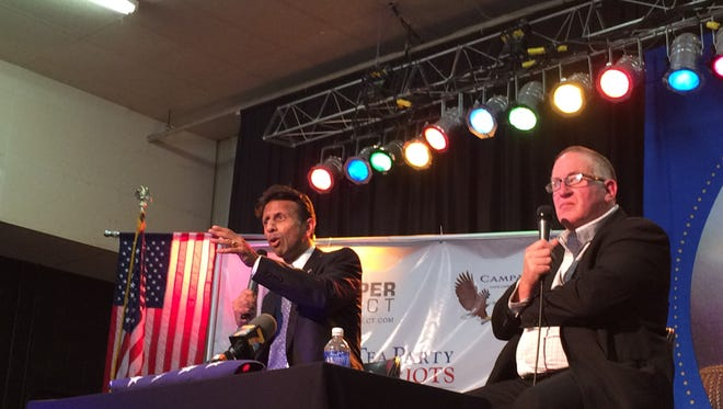 Louisiana Gov. Bobby Jindal, left, sits next to New Zeland political activist Trevor Loudon at the Iowa Grassroots Coalition's Candidate Honest Assessment Summit in Waterloo Saturday, Oct. 24, 2015.