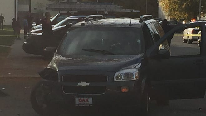 A vehicle with what appears to be bullet holes in the front windshield at the scene of a shooting at Creekwood Apartments on the Northside.