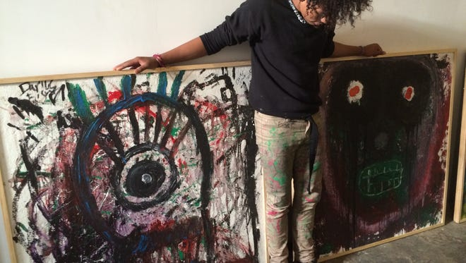 An 18-year-old local artist shows off a few canvases he painted during the past few months at ArtForceIowa's studio on the south edge of downtown.