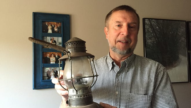 Wayne Kerslake displays one of the train lanterns he has collected over the years. When he was 16, Kerslake purchased a passenger car.