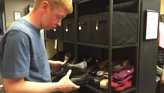 Possibility Place student Zack Craig figures out where to display a pair of shoes at Amelia's Closet, where low-income women are able to find a basic work wardrobe for free.