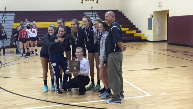 A portion of the Granville volleyball team poses with the Division II district runner-up trophy after the Blue Aces fell to Bishop Hartley.