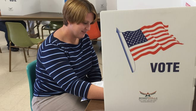 Tara Miller casts her votes for  Woodmore School board members and Sandusky County levies.