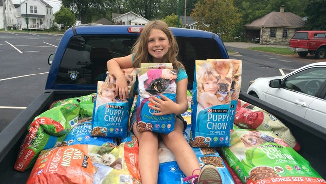 Emma Rokus, 9, daughter of News-Herald Media community engagement editor Jamie Rokus, poses for a picture with donated supplies for the Clark County Humane Society.