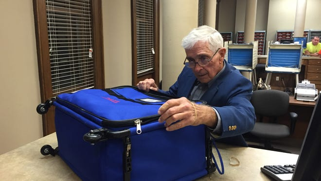 Election Commissioner Charles Phillips opens a box from the Dantzler precinct.