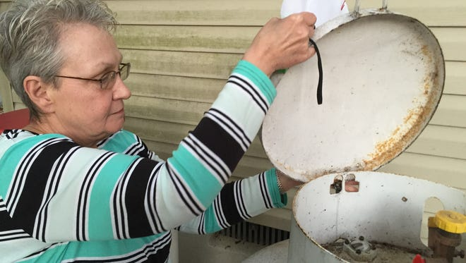 Catherine Toldo of Manchester opens the lif of her old Amerigas propane tank, shortly before the company finally removed it.