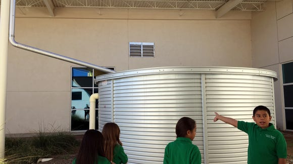 Chester E. Jordan Elementary School fifth-grader Jesus Manuel Castro, far right, explains the school's rainwater collection tank.