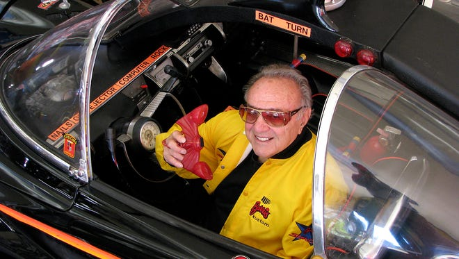 George Barris shows off the Batphone in the driver's seat of the Batmobile from the 1960s TV show.