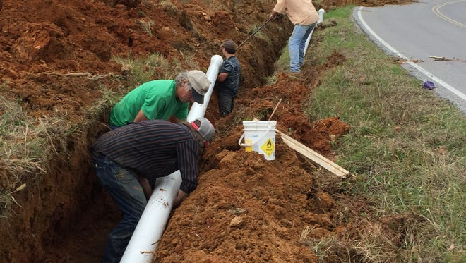 A Whitaker Construction crew installs eight-inch water lines along Buckeye Road as part of a county effort to bring public water to more residents.