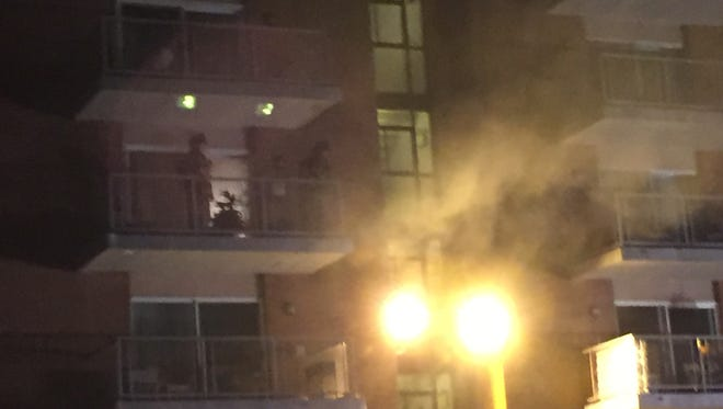 An outside light illuminates smoke pouring from an apartment at River Park Cooperative in Fox Point Friday night.