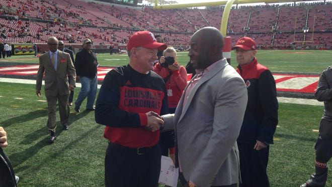 Louisville coach Bobby Petrino greets Elvis Dumervil on Saturday before U of L honored Dumervil's jersey in the first quarter.