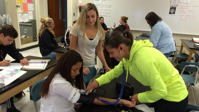 Alyssa Simpkins (right) takes McKaylee Rossetti's blood pressure as Frances Strzemieczny looks on during a class at Millville Senior High School on Oct. 6.