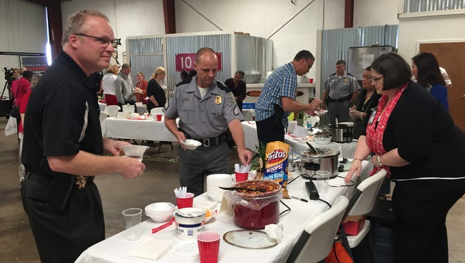 Greenville Co. Sheriff's investigator Stephen Perron and Sgt. Wes Hiott of the state Highway Patrol get a sample of chili during MADD SC's second annual Chili Cook-Off presented by Hot Spot.
