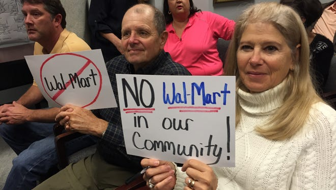 Tom and Nancy Dewey, Canebrake residents, hold signs in opposition to the possible development of a Wal-Mart Super Center just east of the Canebrake subdivision.