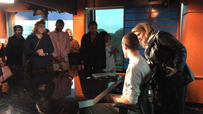 C-Span veteran and current Staunton resident Connie Doebele shows a student how the desk at the Washington Journal studio at C-Span works Monday.