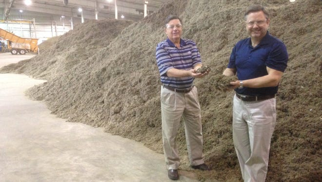 Mark Brown, right, the chief executive officer of WastAway, holds some of the fluff product made from trash while he and Terry Moore, the company's chief business development officer, stand before piles of fluff at their warehouse in Warren County. WastAway uses the fluff to create fuel and potting soil products.