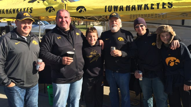 From left to right: Chris Townsend, Aaron Klosterman, John Klosterman, Mark Zimmerman, Wade Chapman and Cade Chapman pose in front of their tailgating home before wrestling and football at Kinnick Stadium Saturday morning, Nov. 14.