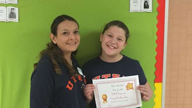 Fifth-grader Katie Carvalho is awarded a certificate by tutor Jessica Muñoz to signify her completion of the Eastwood Heights Elementary School Literacy Camp.