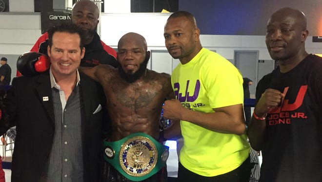 Demond Brock poses with his crew and promoter Roy Jones Jr., second from right, after claiming the WBC-USNBC lightweight championship title Saturday at Southwest University Event Center.
