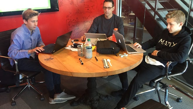 Evan, John and Jensen Burr work on their project Sunday in the final hours of the Startup Weekend at MatchBOX Coworking Studio.