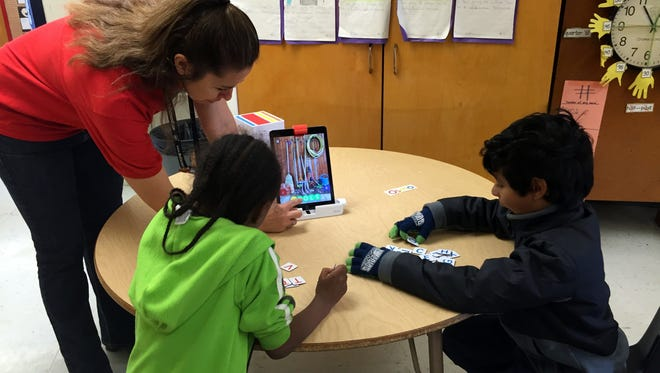 Teacher Stormy Daniels works with her students on a spelling game on an iPad.