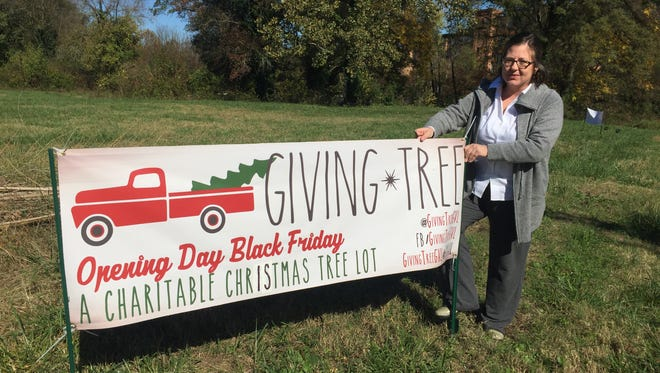 Kim Warren-Page sets up  signage for Giving Tree Greenville, which opens at 420 Mills Ave. on Nov. 27.