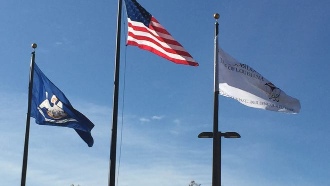The Tunica-Biloxi tribal flag (right) flies beside the United States and Louisiana flags outside of the Tunica-Biloxi Cultural and Educational Resource center on the tribe's reservation near Marksville