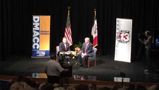 Donald Trump speaks with David Price of WHO-TV at a town hall in Newton, Ia.